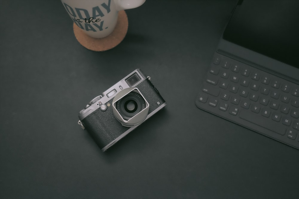 black-and-gray camera on table near tablet keyboard case