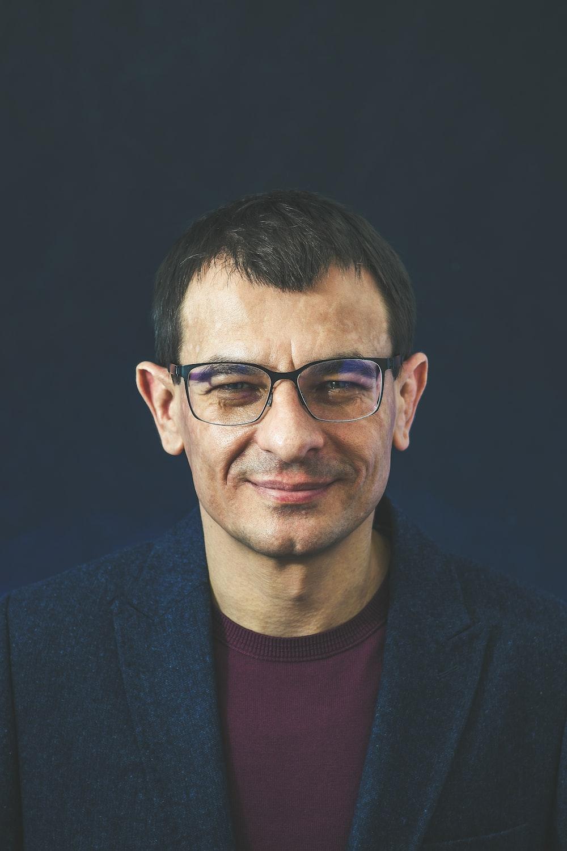 smiling man wearing black framed eyeglasses