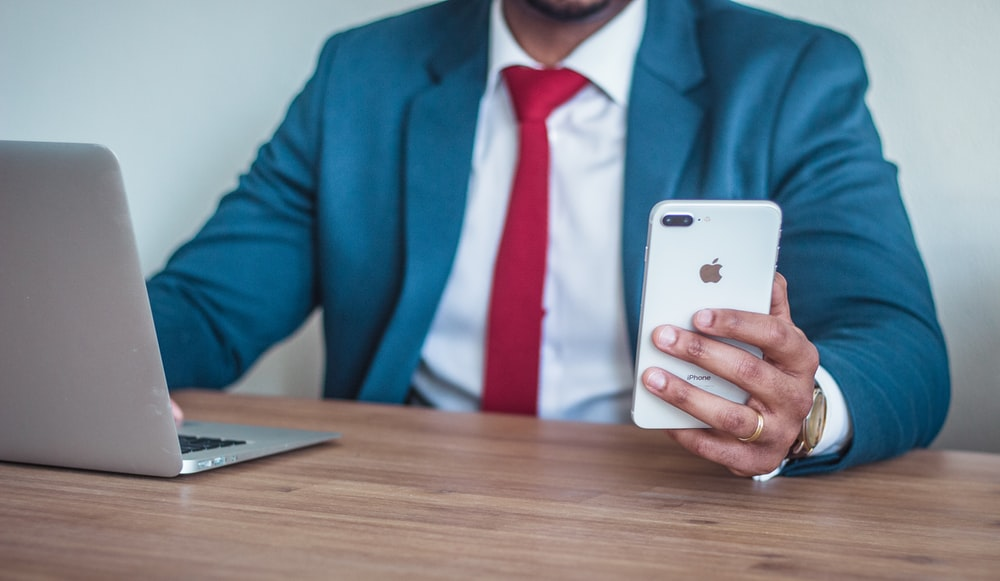 man sitting beside table holding silver iPhone 7 Plus