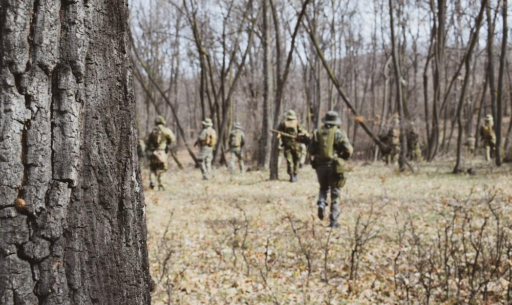 soldiers walking near trees