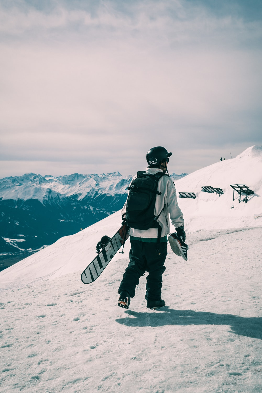 man holding snowboard on snow covered field