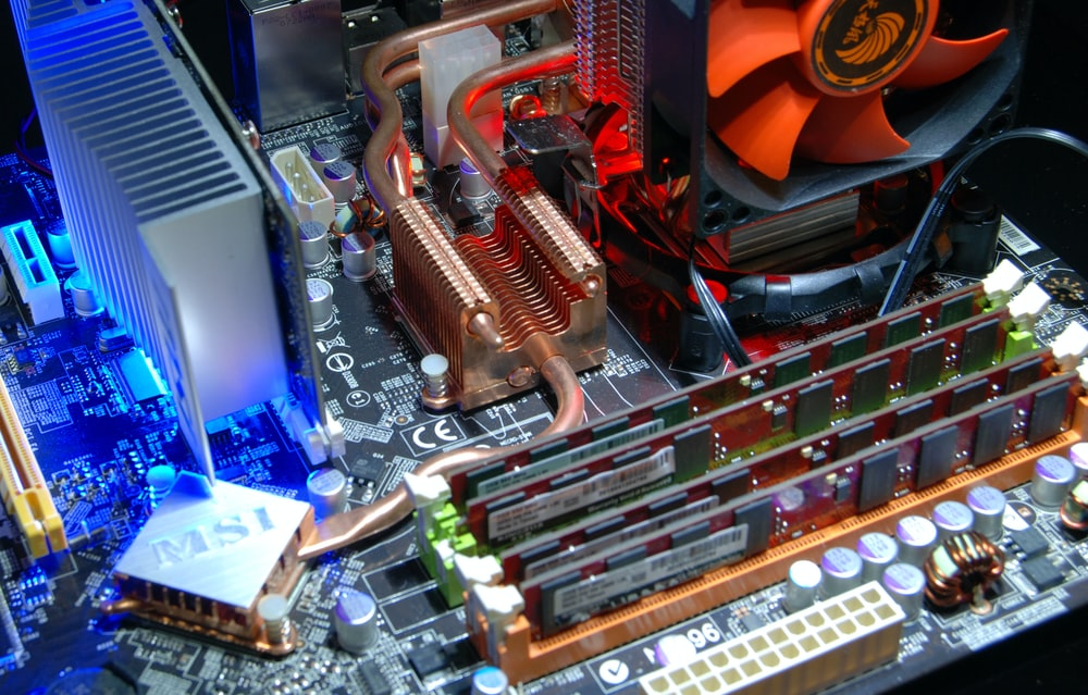 computer motherboard with RAM sticks and aftermarket cooling system