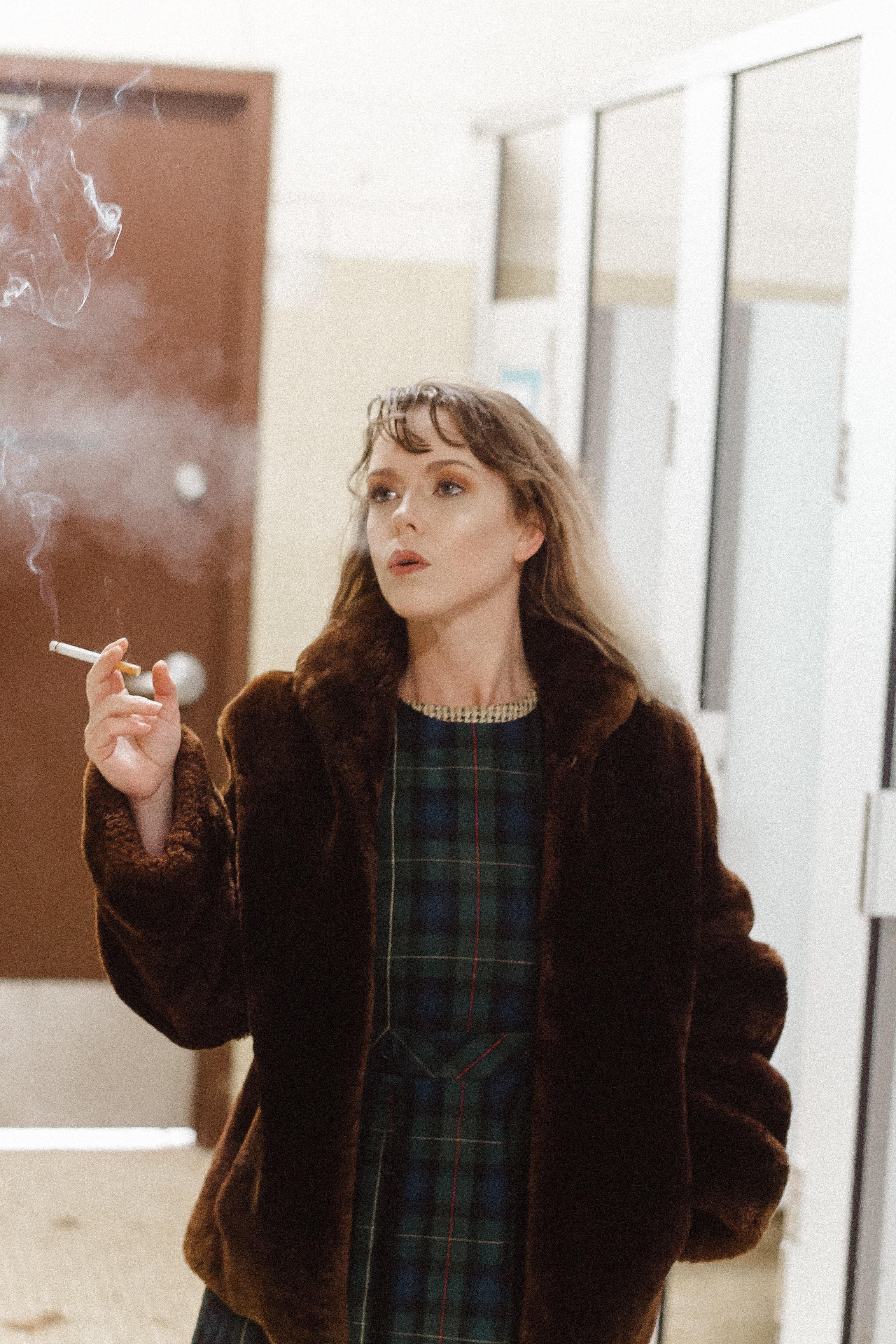 woman smoking by glass hallway