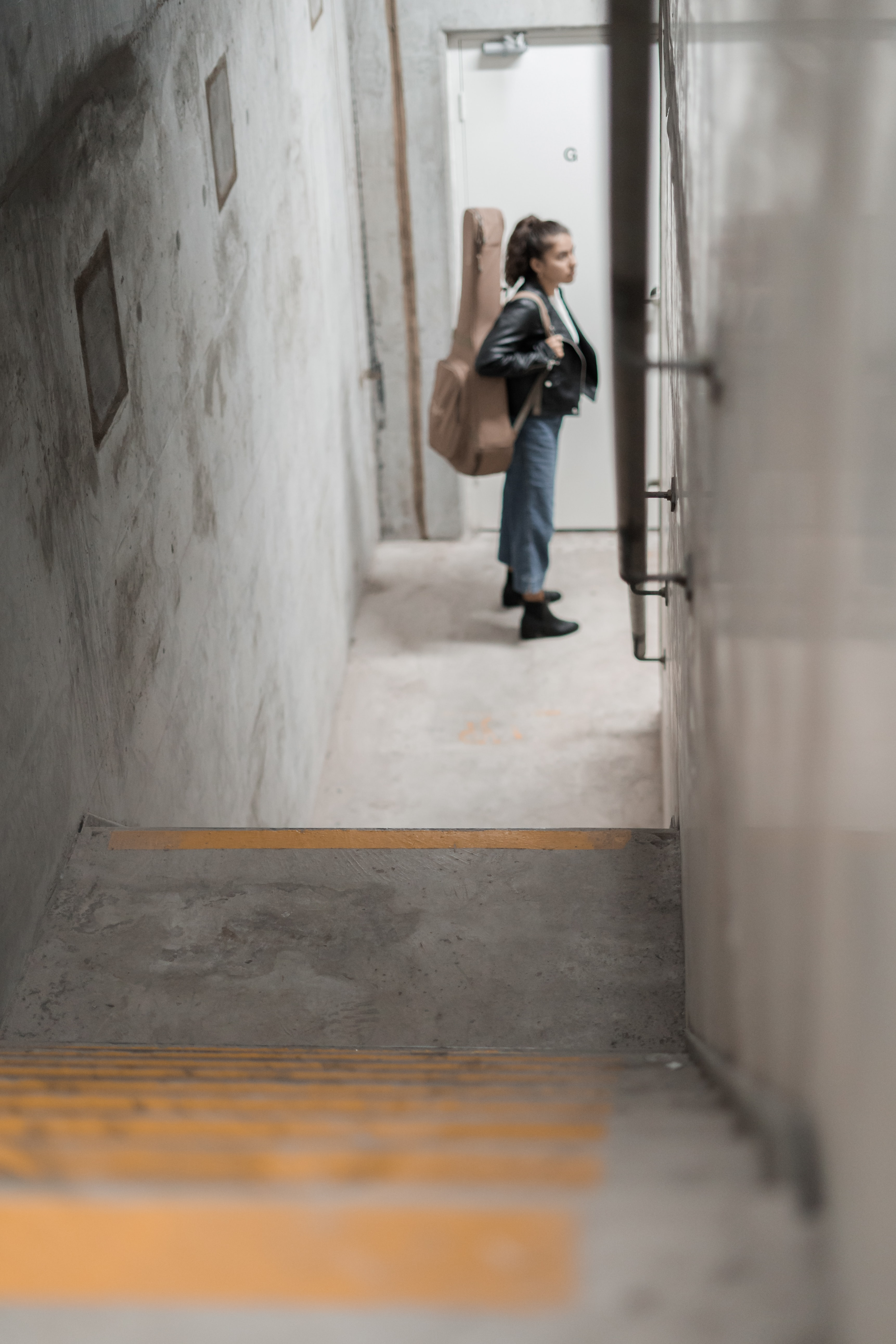 woman carrying brown acoustic guitar gig bag by the door