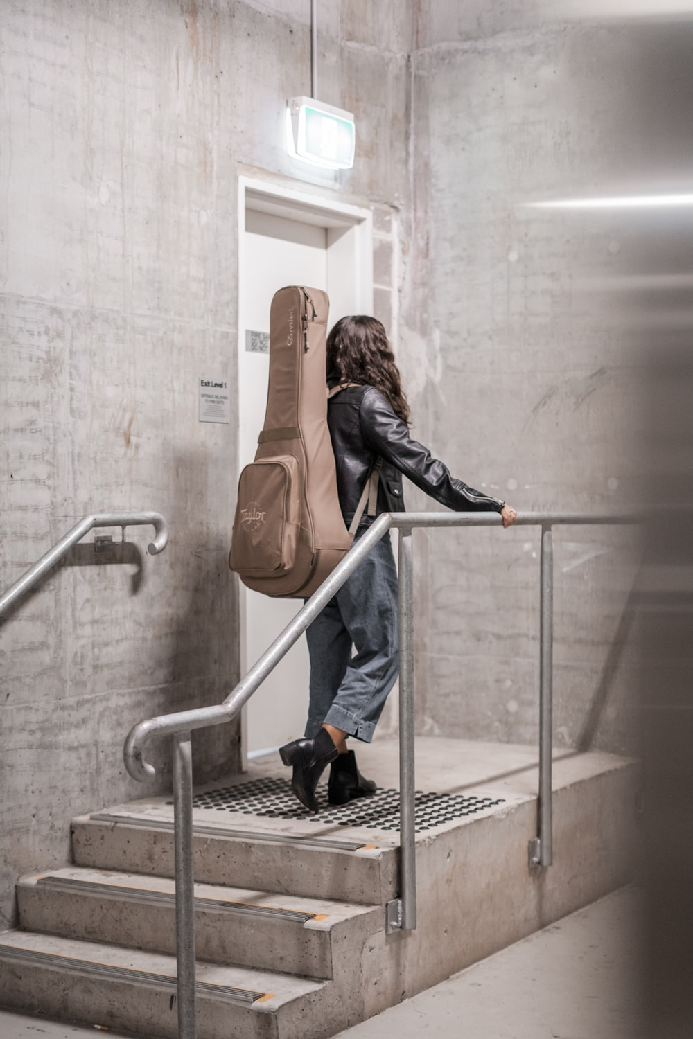 woman carrying brown gig bag standing near closed door