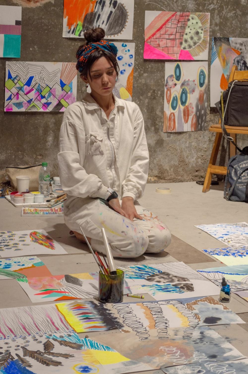 woman sitting near painting lot