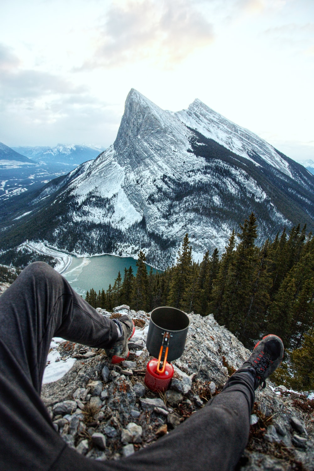 person sitting on edge of mountain during daytime