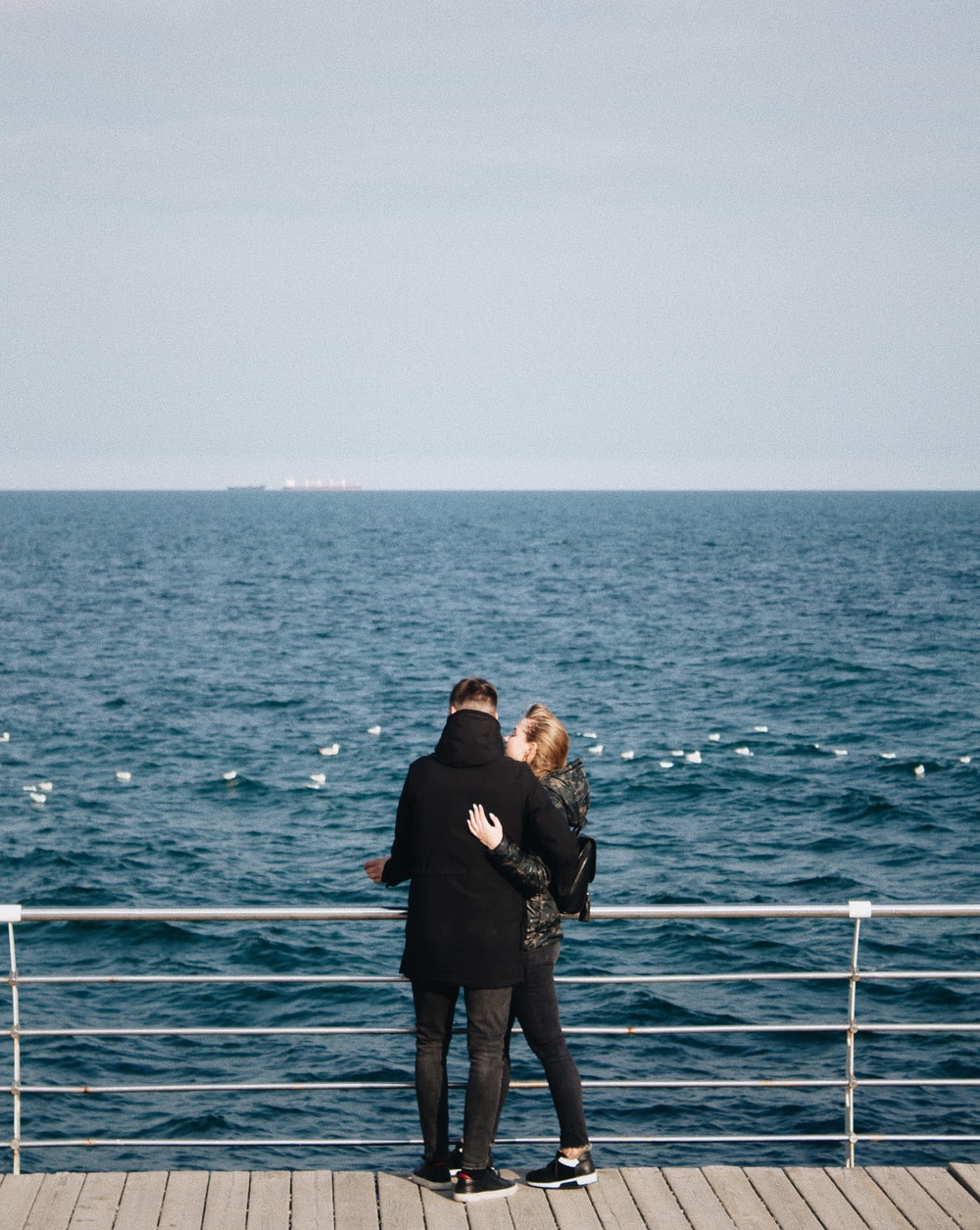man and woman standing in front of body of water