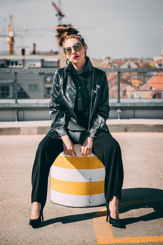 woman sitting while wearing black leather jacket