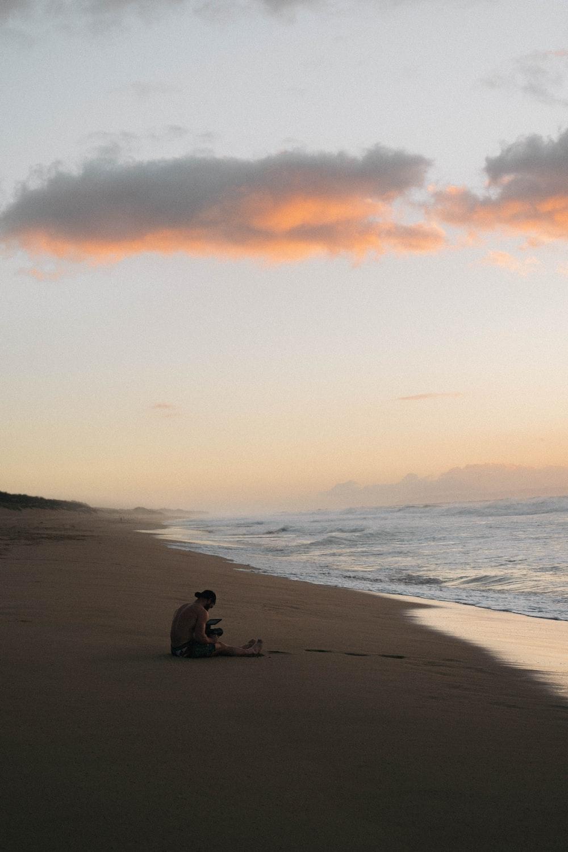 man sitting on seashore during sunset