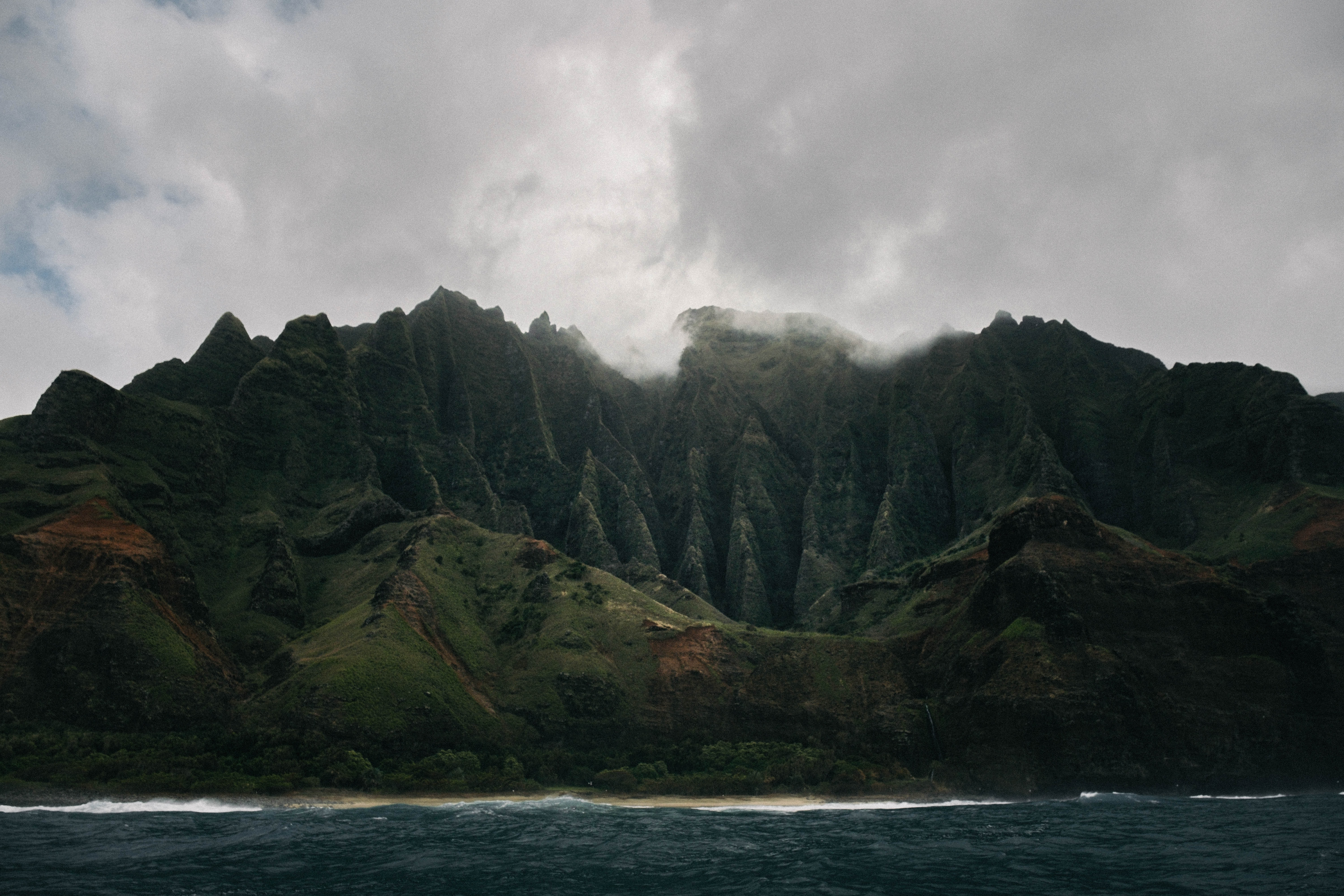 grey clouds hovering above mountain island