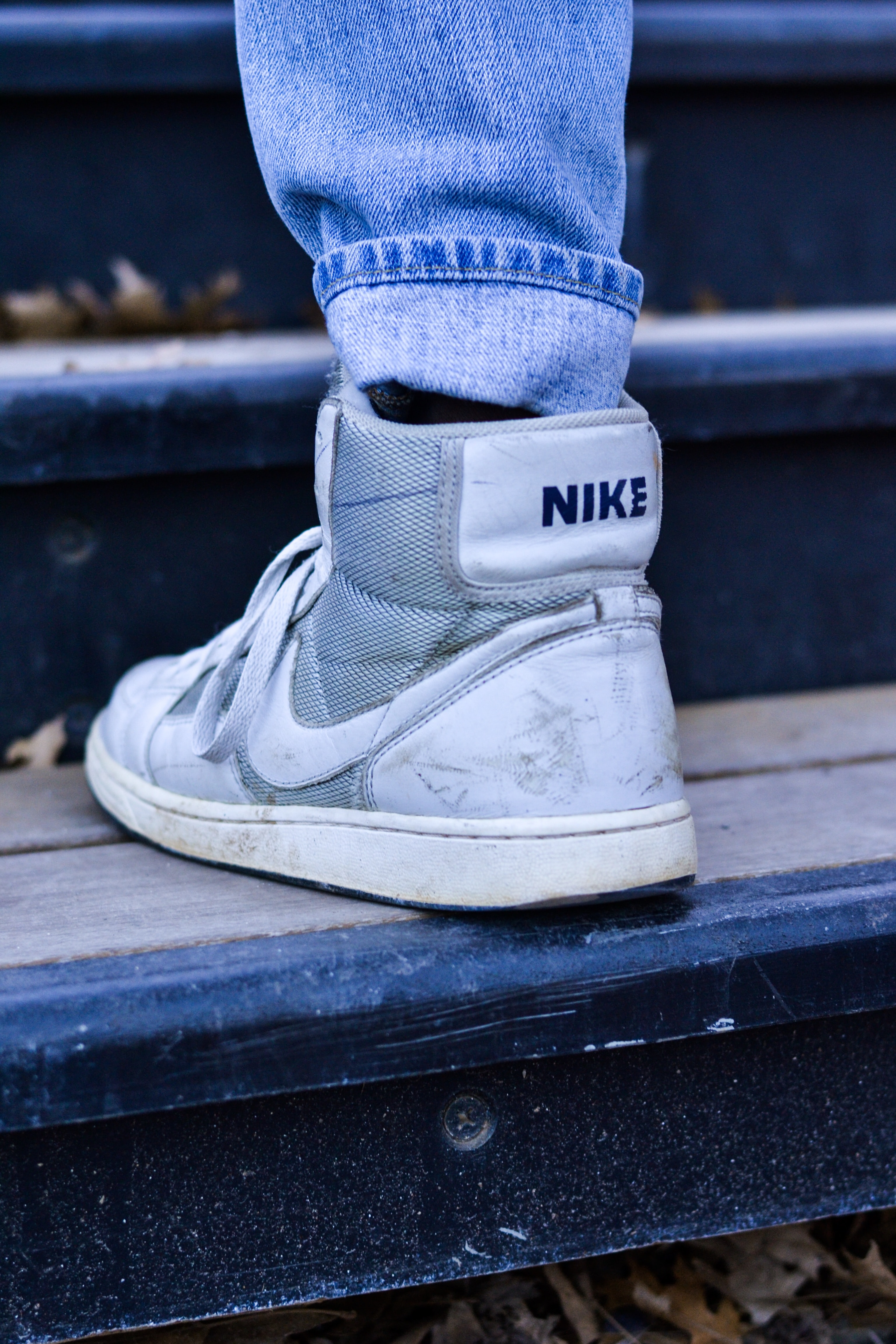 person wearing white and gray Nike sneakers