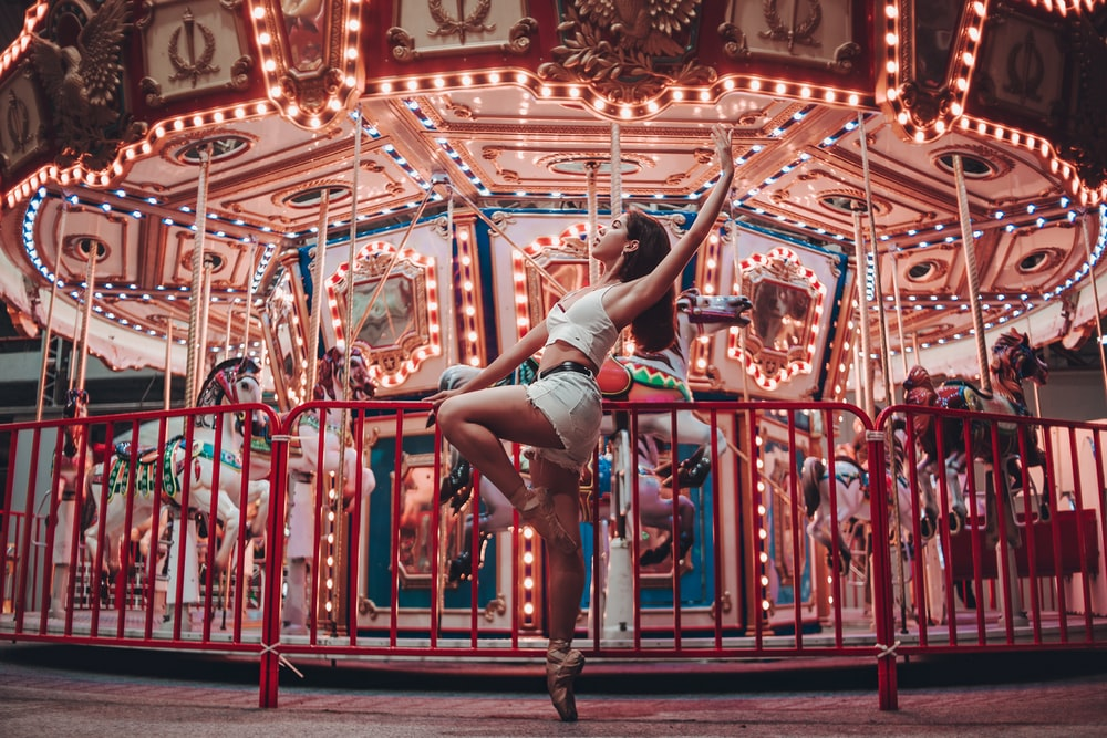 woman sitting on metal rails by turned on merry-go-roudn