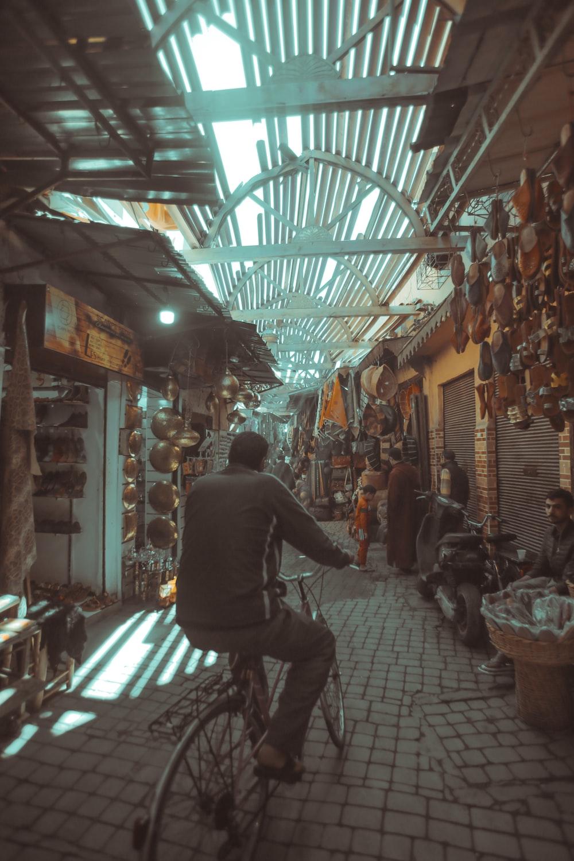 man riding bicycle between stores