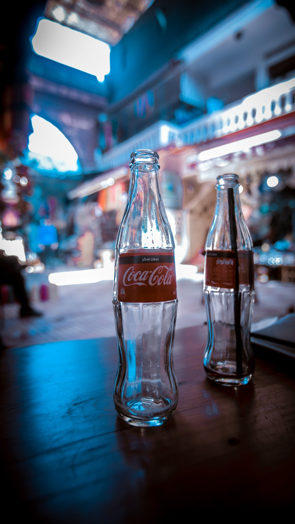 two empty Coca-Cola soda bottles on brown table