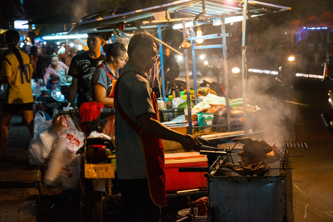 A food stall operator grilling chicken at the night market in Vientiane, Laos