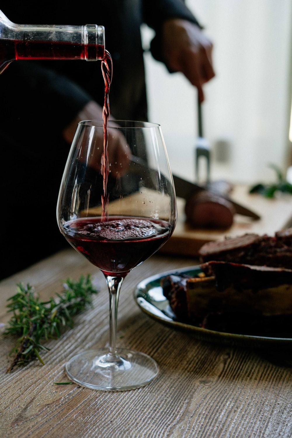 человек наливает красное вино в бокал