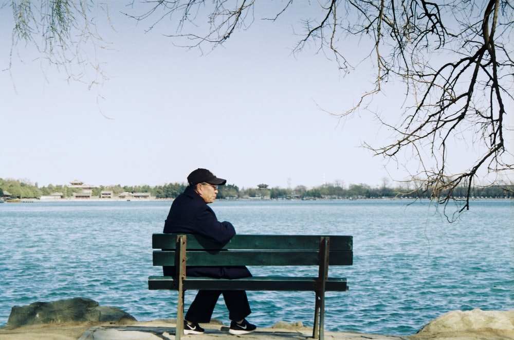 man sitting on blue wooden bench