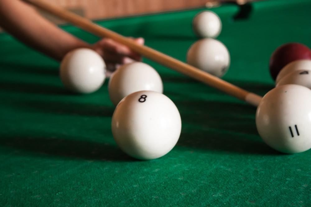 white billiard balls beside cue stick