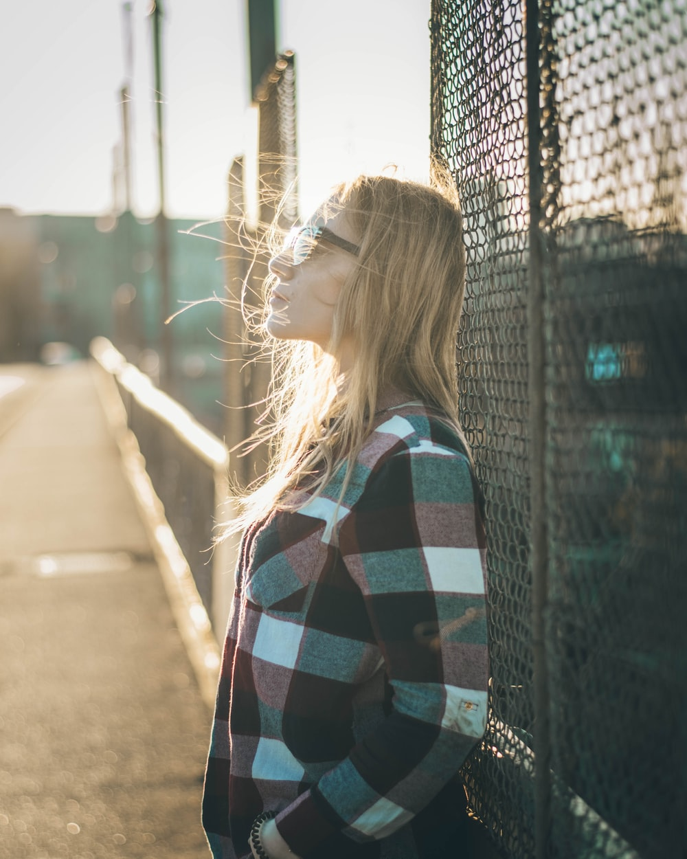 woman standing beside chain link fence