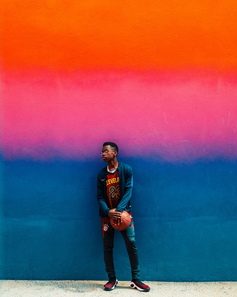 boy standing and holding basketball beside blue and pink painted wall