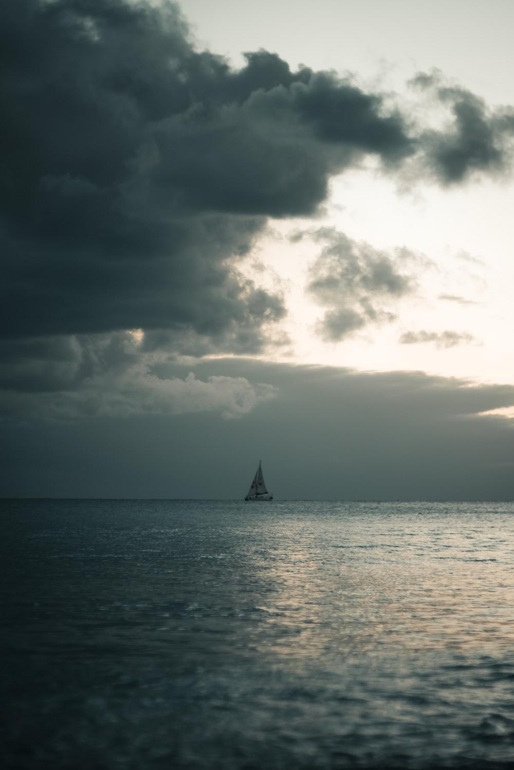 sailing boat under nimbus clouds