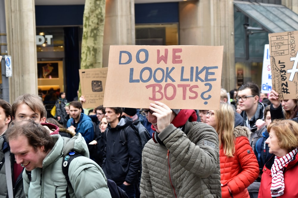 woman holding cardboard box with do we look like bots ? text