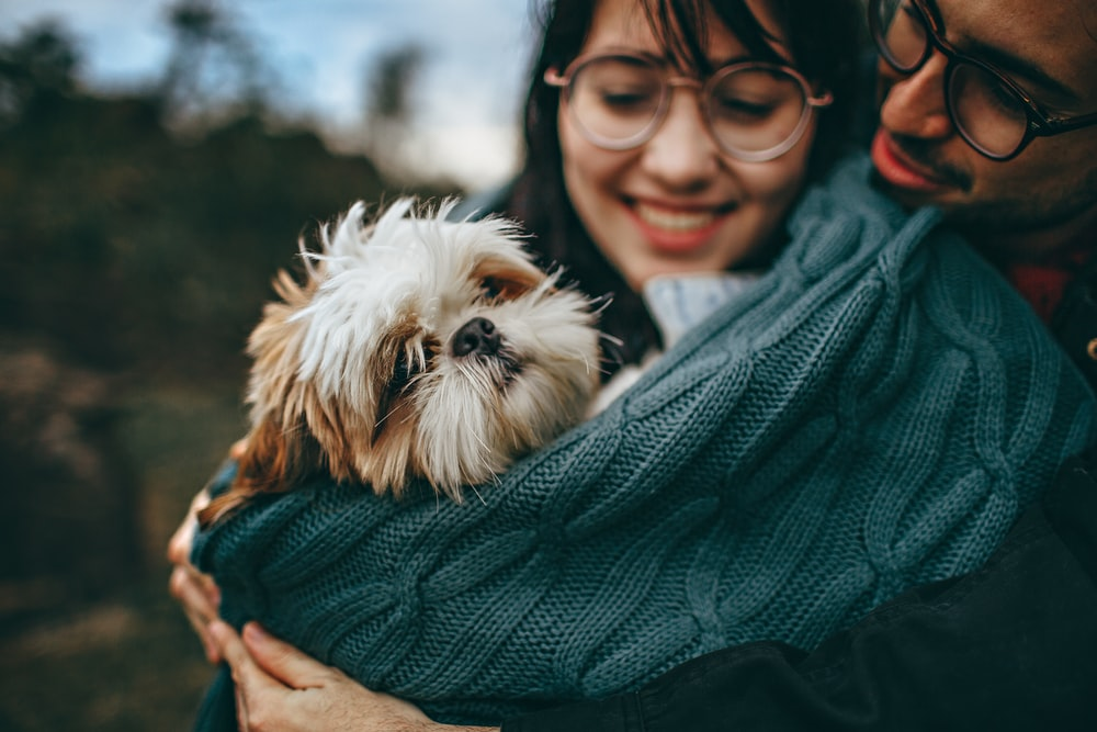woman carrying dog