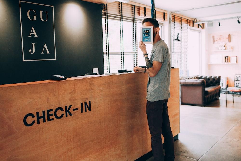 man standing beside counter