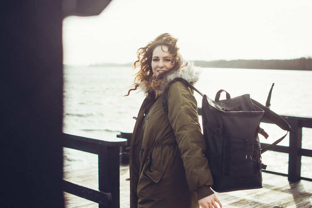 selective focus photography of woman carrying black backpack