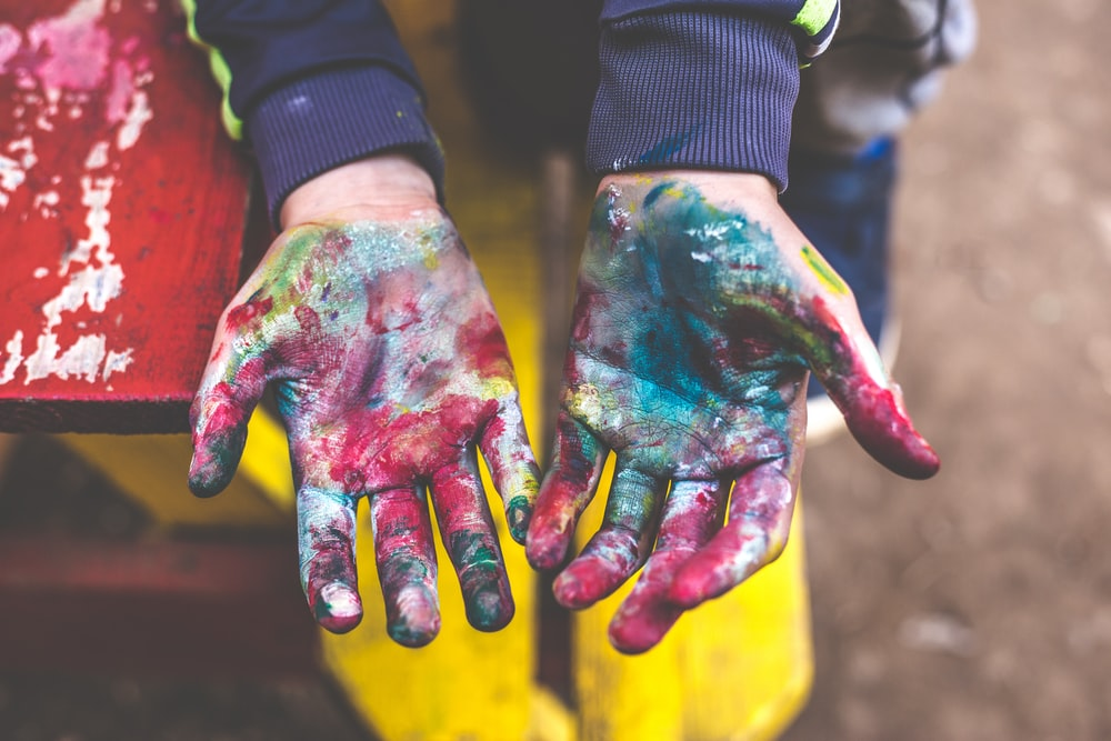 person showing both palms with paints