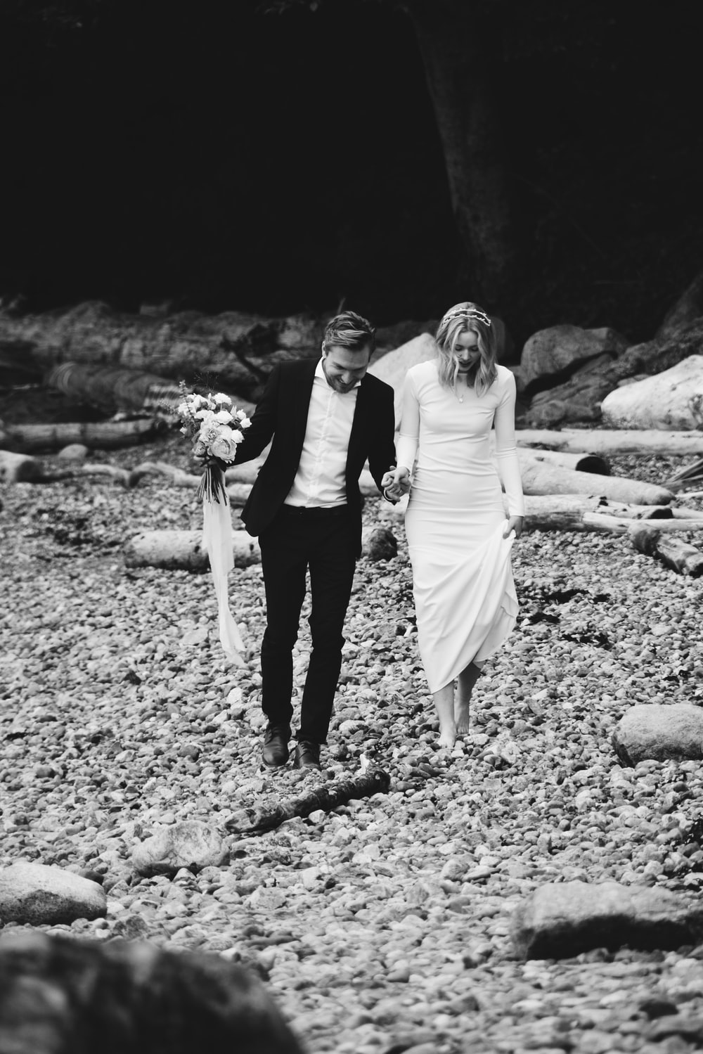 grayscale photo of bride and groom walking