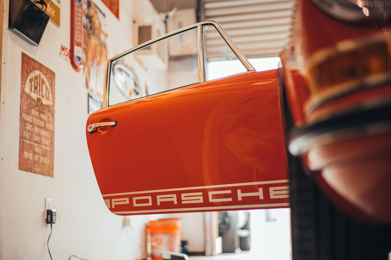 open door orange Porsche inside garage