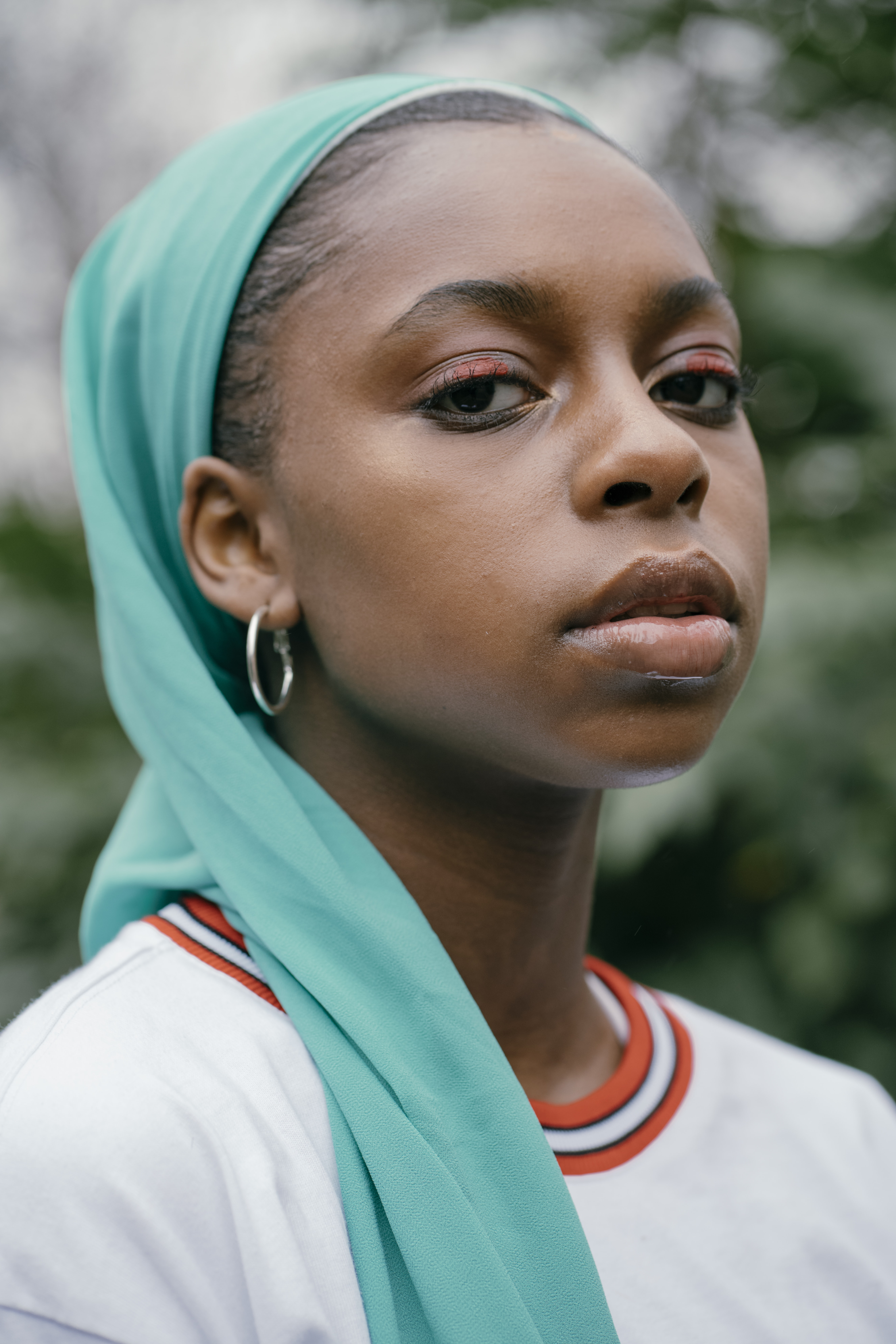 woman in orange and white crew-neck shirt and green headscarf