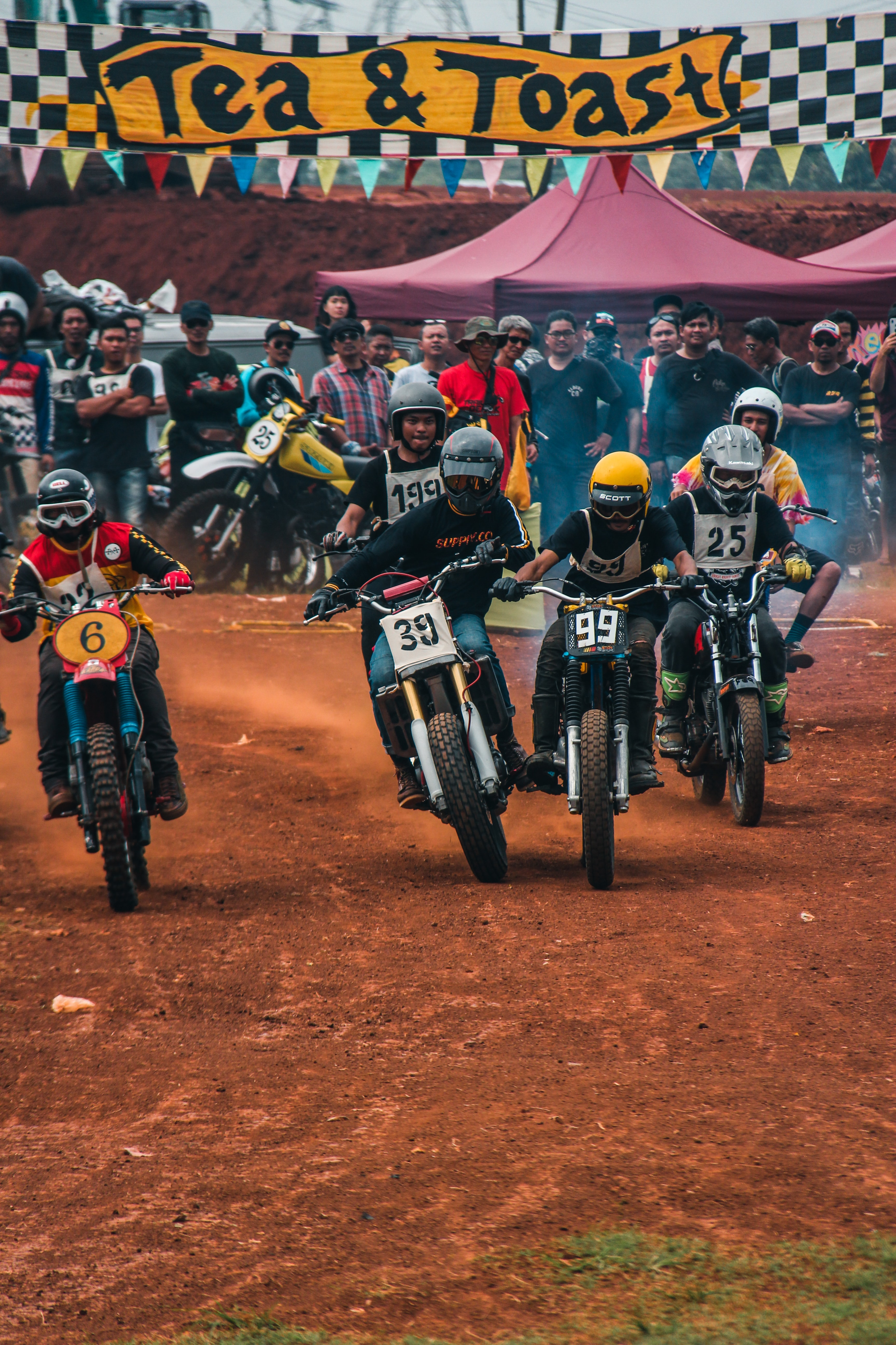 person riding dirt bikes in dirt bike competition on dirt track during daytime