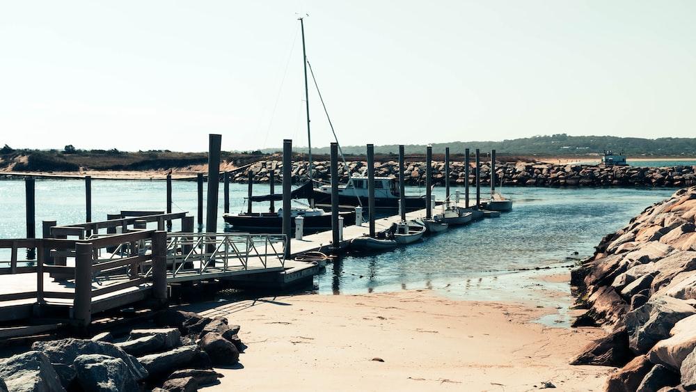 gray wooden dock beside motor boats during daytime