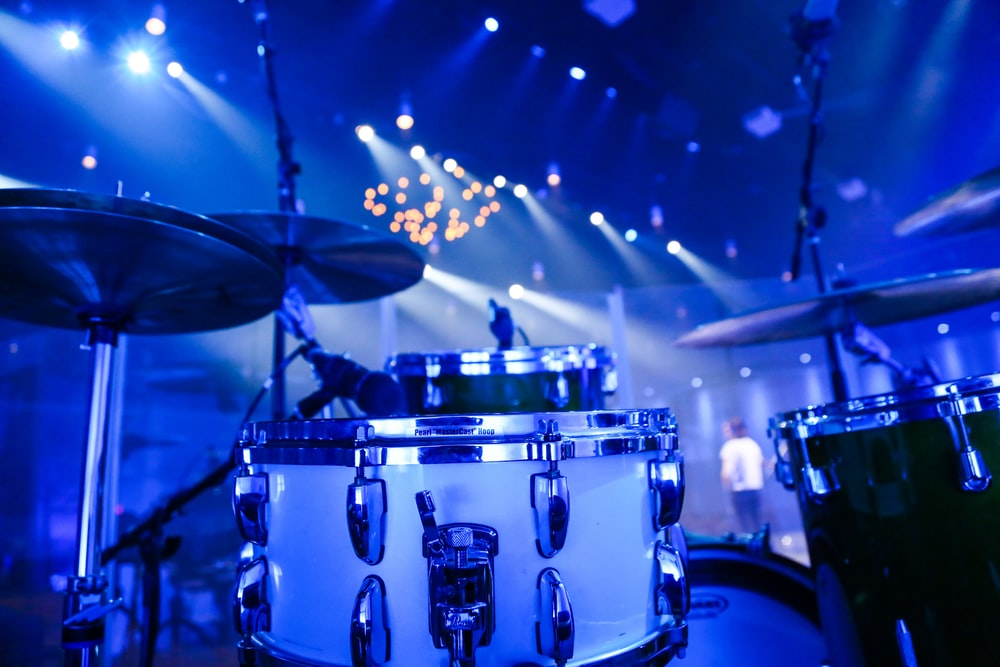selective focus photography of white acoustic drum kit