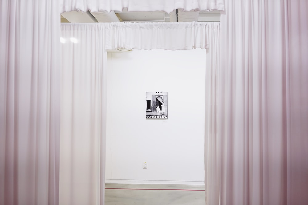 portrait on wall seen through the white curtains