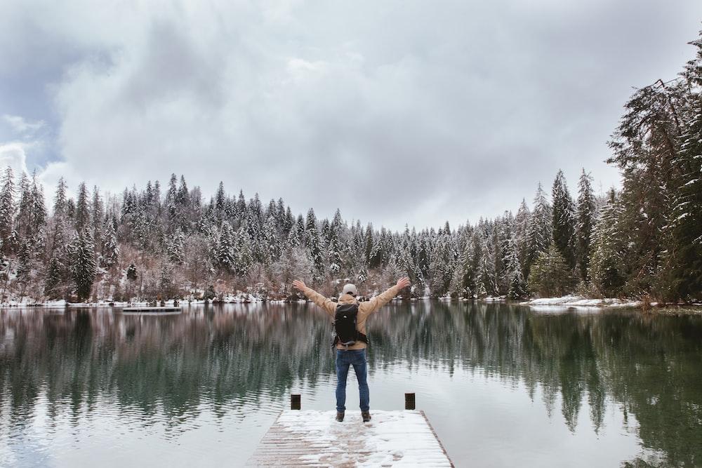 man standing on edge of dock near lake during daytime
