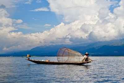 man on boat with fish catcher under cloudy sky myanmar zoom background