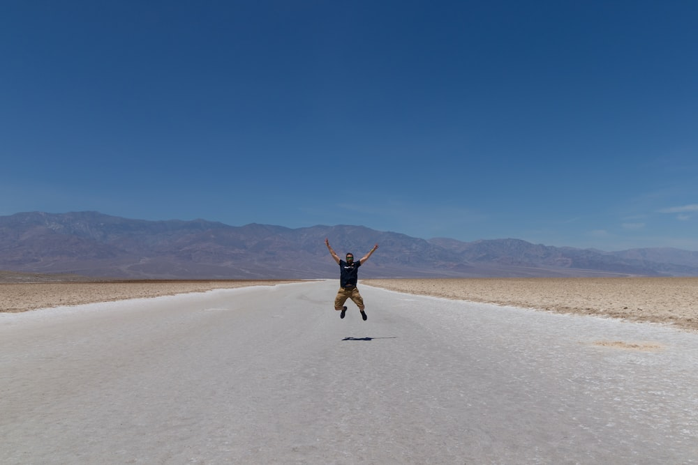 man jumping in middle of empty country road