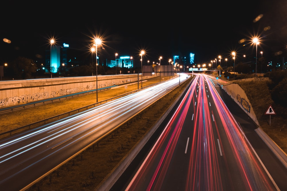 lighted cars passing highway