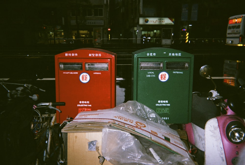 two green and red boxes standing near two motorcycles