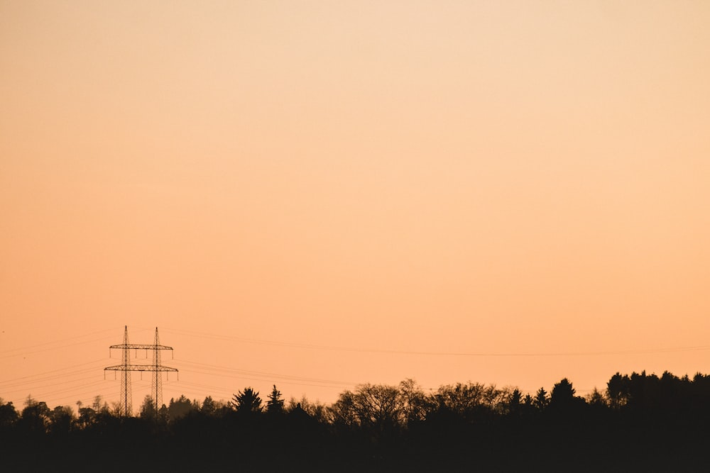 silhouette of transmission tower over the trees