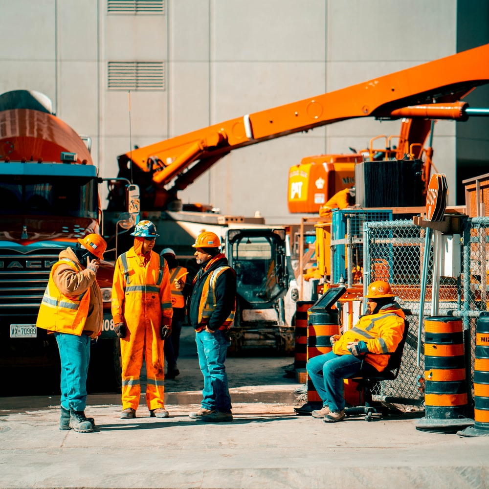 four men stands beside parked concrete truck and excavator