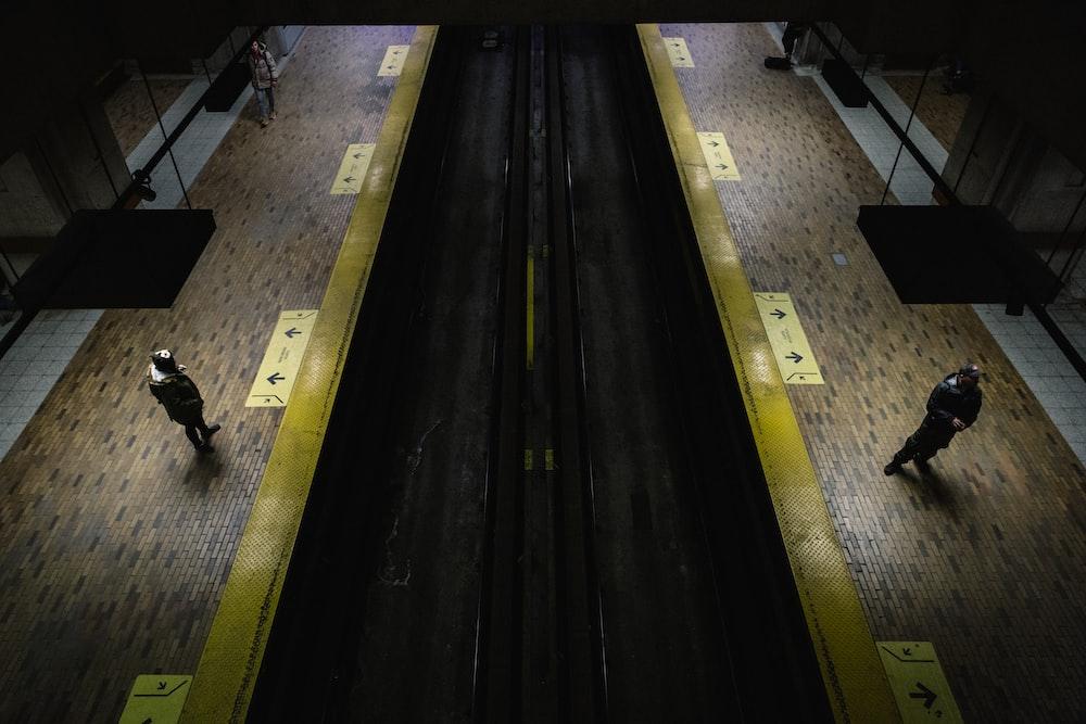 two men standing beside train railway