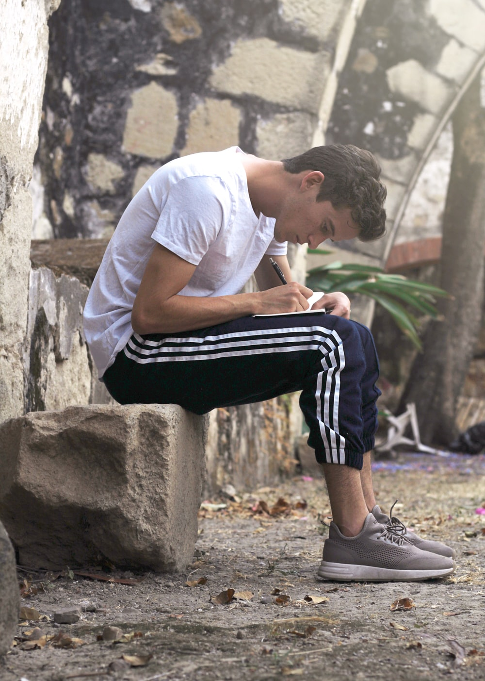 man sitting on stone writing down