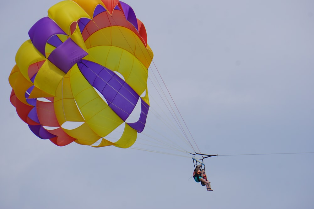 people riding parasailing