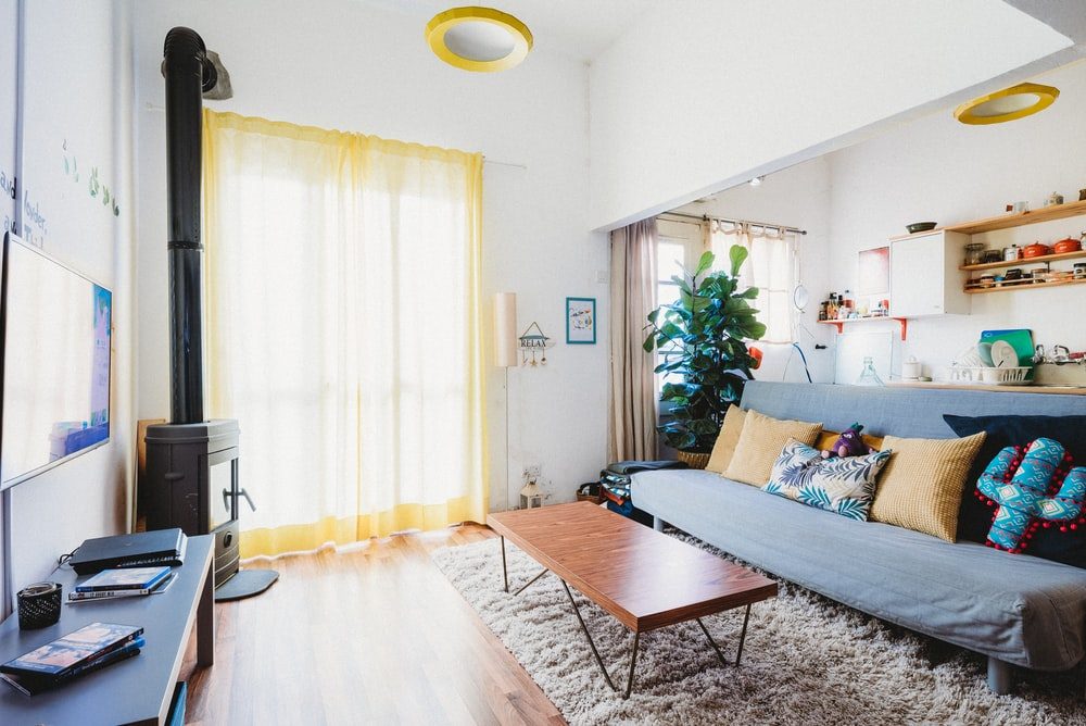 assorted-color throw pillows on armless futon in living room are of the house