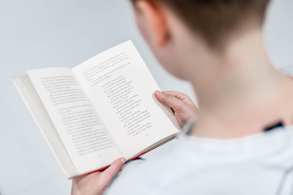 person in white holding book reading